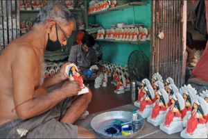 During lockdown an artist gives finishing touches to an idol at Kumartully workshop in Kolkata.